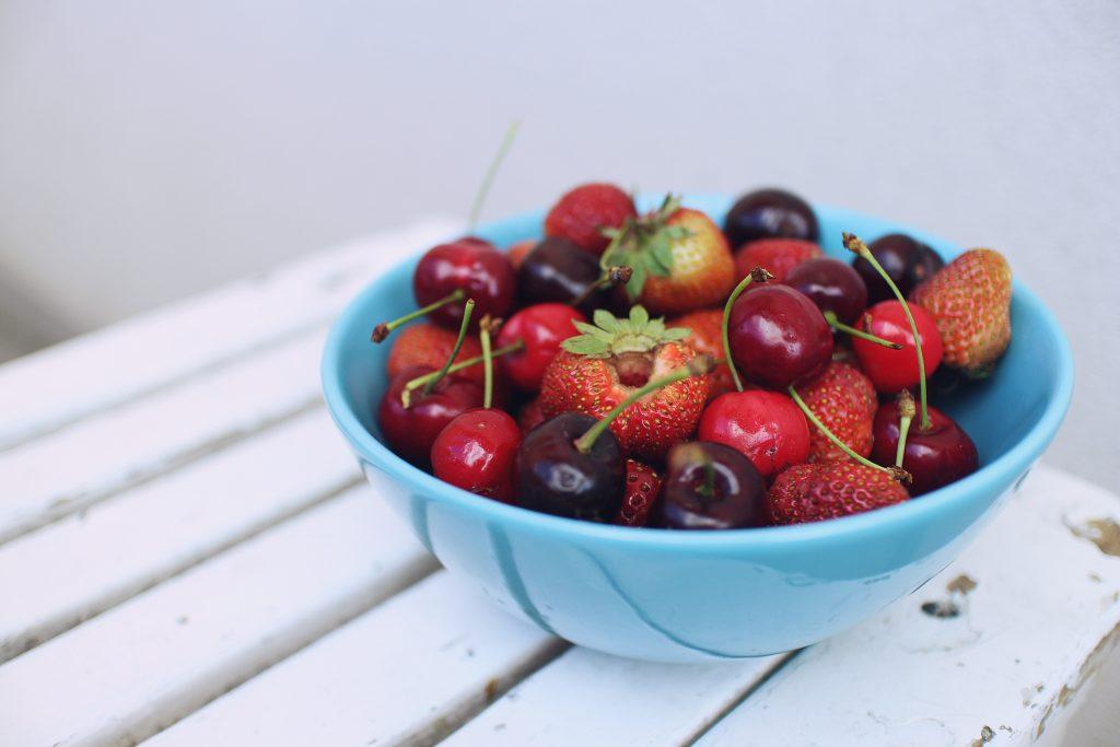 Des fraises et cerises dans un bol